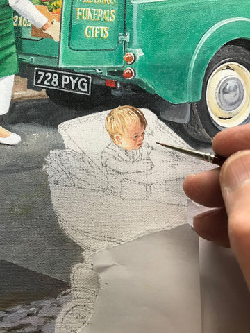 A close up of Trevor painting his grand-daughter in her pram