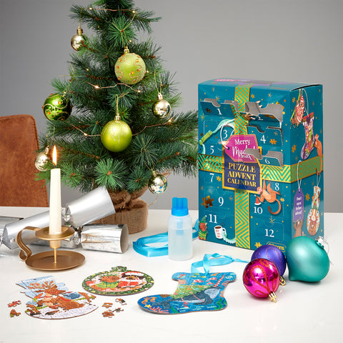 Merry Mischief advent calendar on a table with some baubles, a Christmas tree and 3 of the jigsaws in front of it.