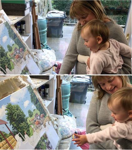 Two images of Trevor's wife holding his grandaughter while looking at some unfinished artwork