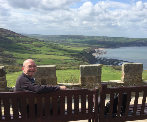Trevor looks at the camera smiling. Behind him is the view of the Yorkshire Coast, towards Robin Hood's Bay