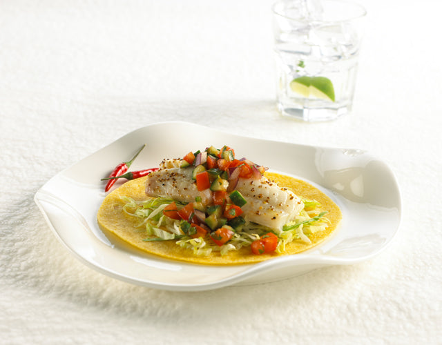 High Liner Pollock on a corn tortilla with vegetables and served on a white plate