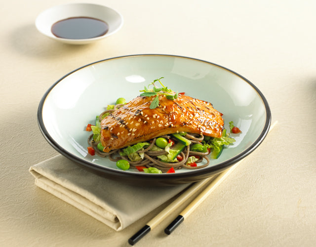 High Liner Salmon served with a glaze on top of a bed of vegetables in a bowl next to chop sticks and soya sauce
