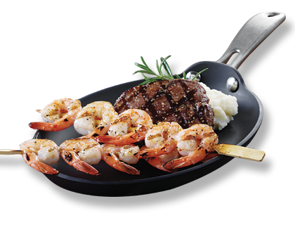 Mirabel Shrimp Skewers cooked and served on a pan next to a piece of steak