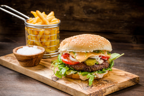 Bruss sirloin burger on a bun with toppings and served on a wood board next to french fries and dipping sauce