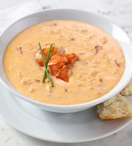 Bowl of Campbell's Verve Lobster Bisque topped with lobster and chives, on a white plate with bread