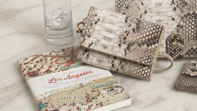 A card holder, jewelry, and cosmetic bag resting on a bathroom countertop with a Los Angeles Travel Guide