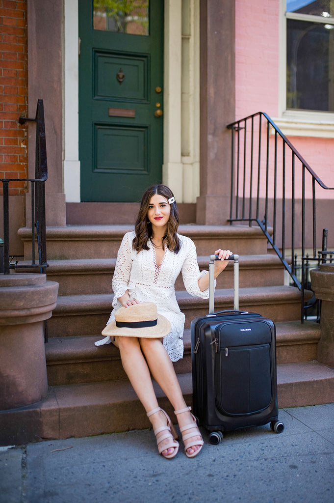 Esther Santer with Ricardo Cupertino Hybrid Luggage Collection - sitting on a stoop in NYC next to carry-on suitcase