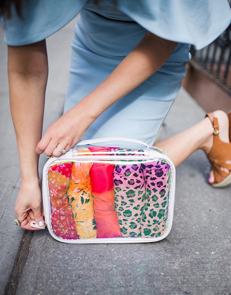 Esther Santer with Stephanie Johnson Miami Collection - zipping up a clear, stylish bag for organized packing