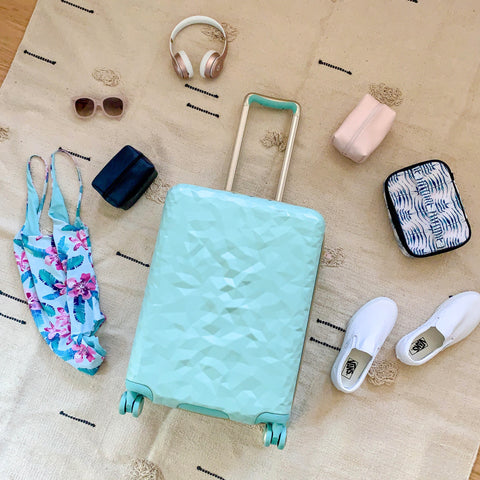 Flatlay image shows a mint Indio carry on suitcase surrounded by sunglasses, headphones, a swimsuit, and Indio train case accessories.