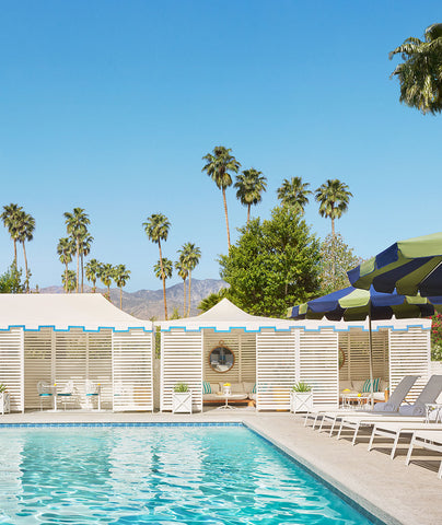 Image shows a pristine blue swimming pool under a cloudless sky lined with white lounge chairs and cabanas.