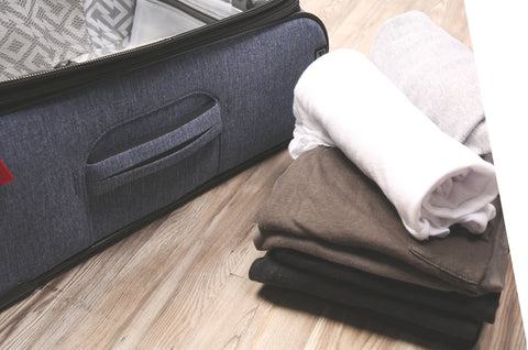 Rolled clothes next to suitcase