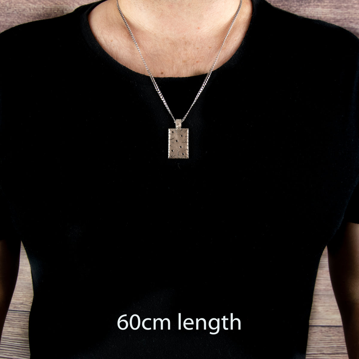 Silver, heavy pendant with hand engraving and black diamonds. On 60cm chain on persons chest