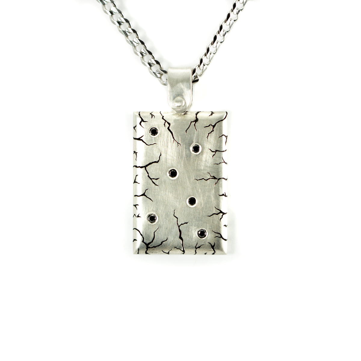 Silver, heavy pendant with hand engraving and black diamonds. On chain