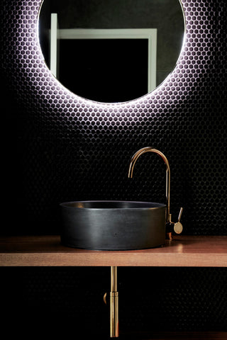 Concrete black basin with gold tap