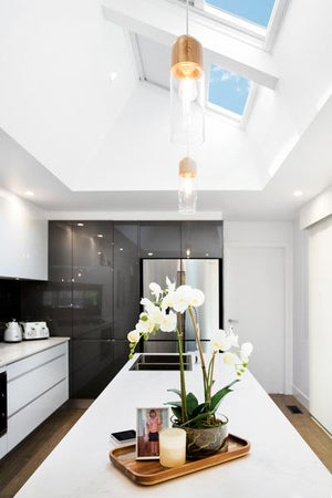 Kitchen design featuring pitched skylights and blockout blinds
