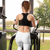 Fitness woman working out in custom print black padded sports bra and white yoga pants.