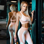 Blonde fitness model posing in gym during a workout wearing custom matching pink sports bra and workout leggings. Purchase on sale at BuckleyBear.com