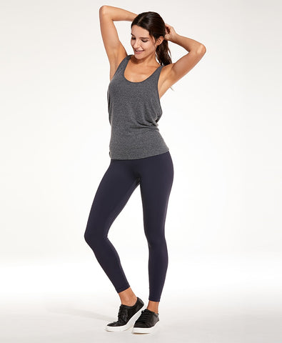 woman posing in navy blue high waist yoga leggings and racerback tank top