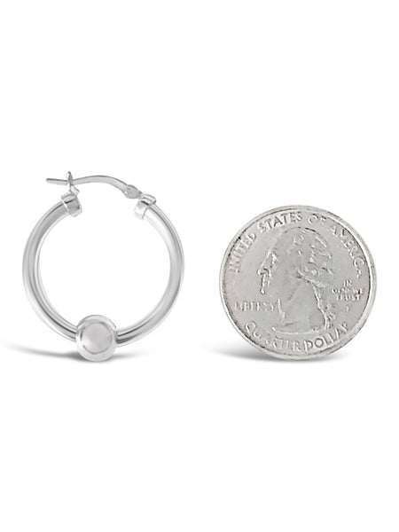 Cape cod hoop earrings measuring against a quarter