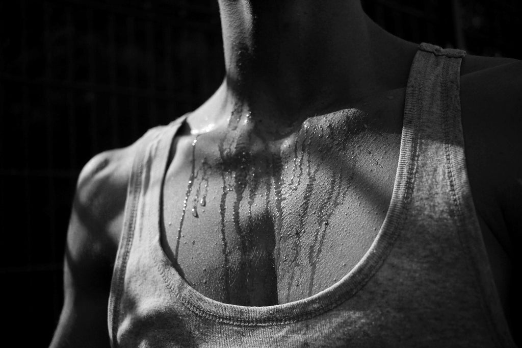 Front view of a man wearing a white vest sweating post exercise