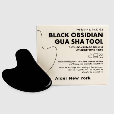 black obsidian Gua sha tool next to Alder New York product packaging