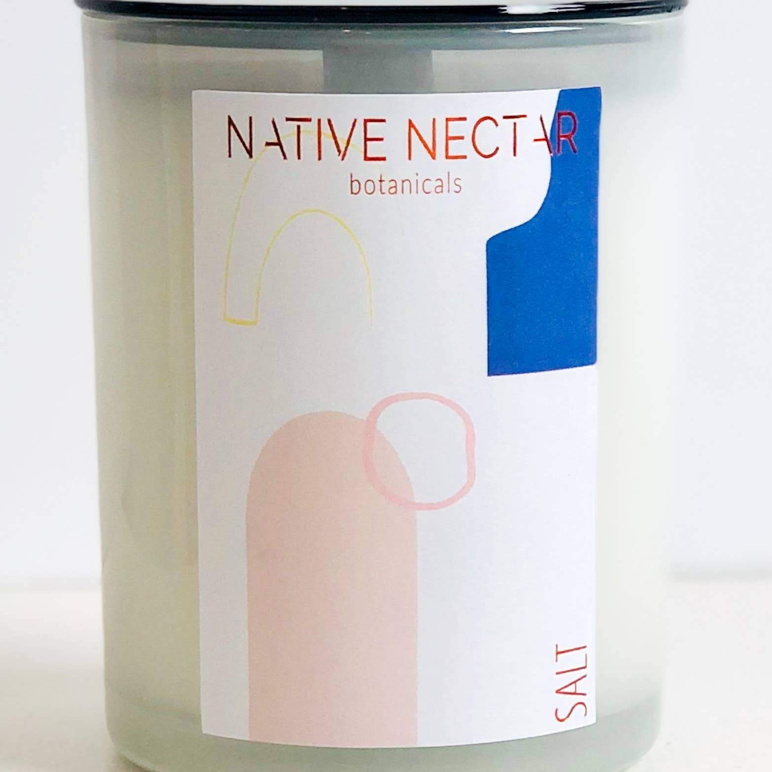 wood wick candle in clear glass jar with pink blue and white graphic design label