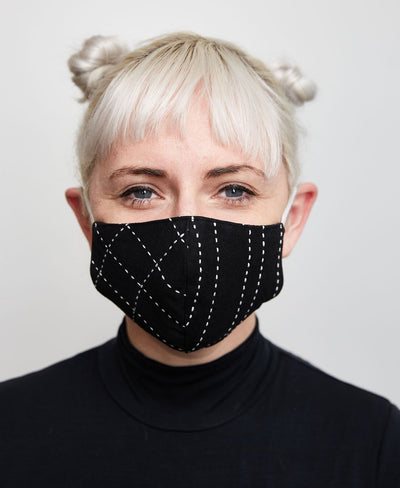 Black face mask with cross stitch pattern on woman's face