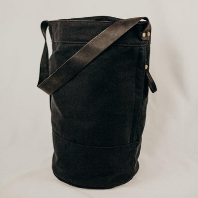 black canvas bucket bag with black leather strap