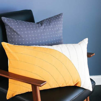 Pillow with gold curve overlay pattern on chair