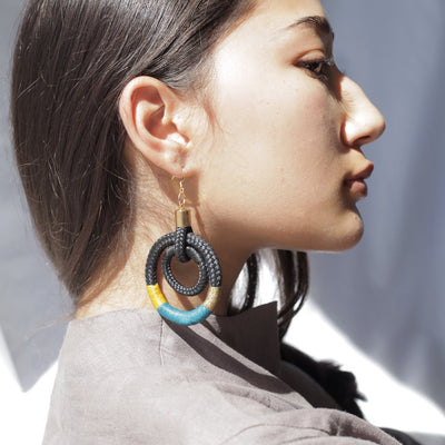 black, blue, and orange knot hoop earrings on woman