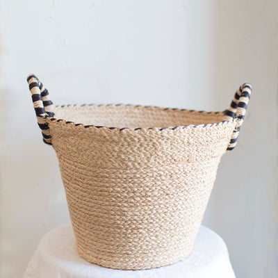 Natural handwoven basket with black outer stitching on raffia fibers