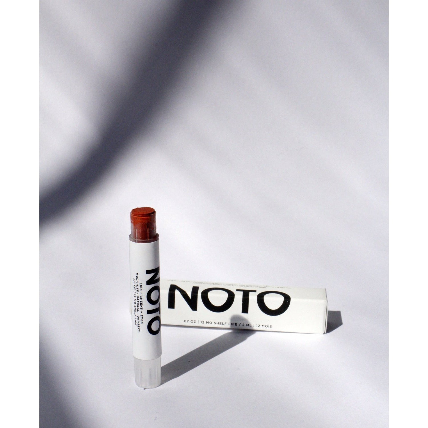 noto lip and cheek stain stick next to box container