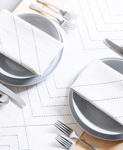 Stitched pattern on creme colored napkin with silverware