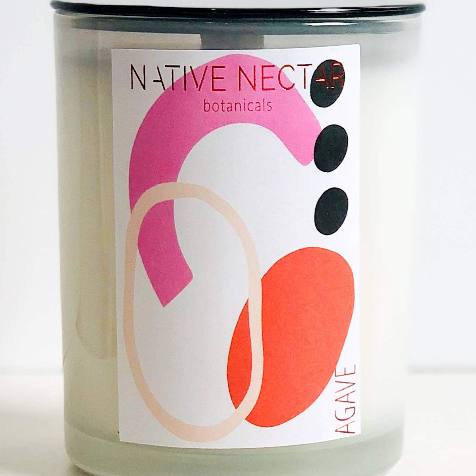 wood wick candle in a clear glass container with pink, orange, black and white graphic design label
