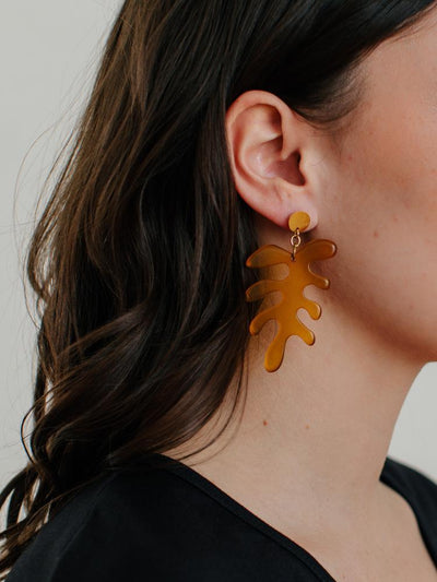 resin and brass amber colored leaf earrings on woman