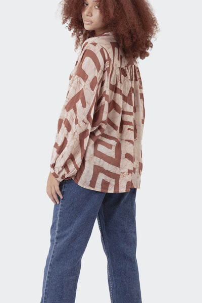 brown block patterned and white long sleeve button down shirt on woman back view