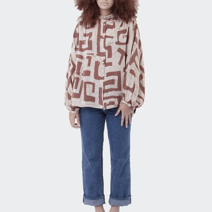 Hand printed batik brown pattern on a pink long sleeve blouse ethically handmade by Ose Duro in Ghana