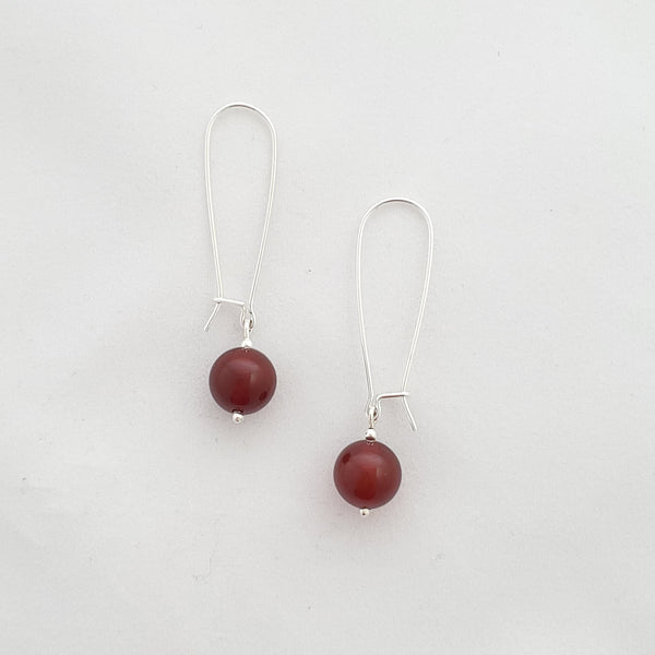 Round orange-red carnelian beads drop from long sterling silver earring wires