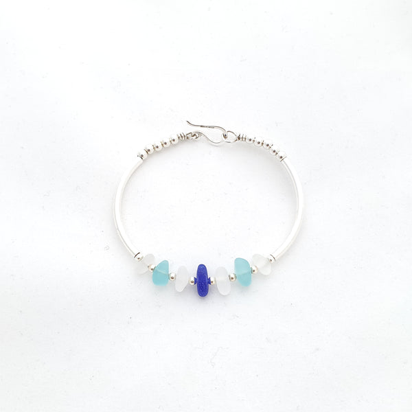 Sea glass pieces in white, blue, and aqua as the centerpiece and silver tubes along the sides, finished with a hook clasp. Oval bangle bracelet.