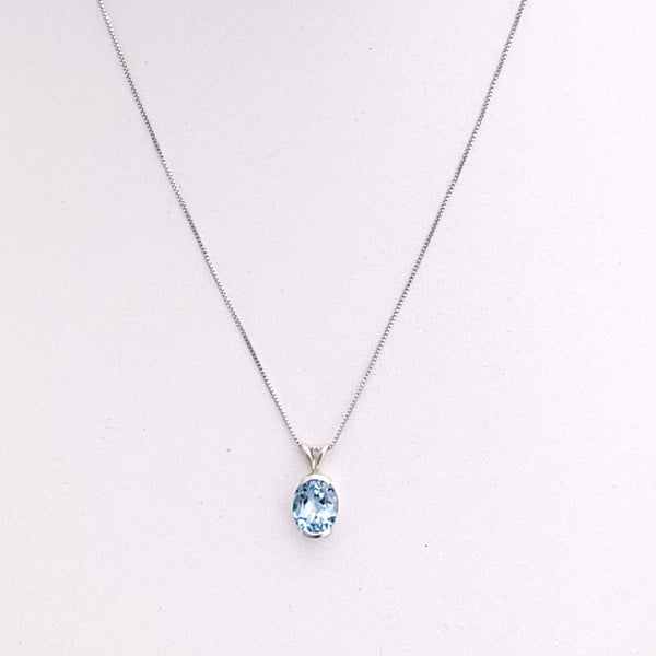 Oval blue topaz pendant set in a sterling silver half bezel setting on box chain.