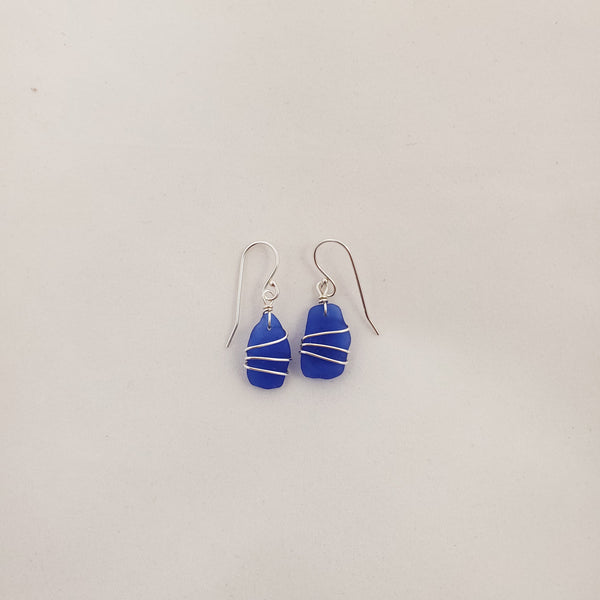 Cobalt blue sea glass with 3 layers of silver wire wrapped around hanging from french earring wires