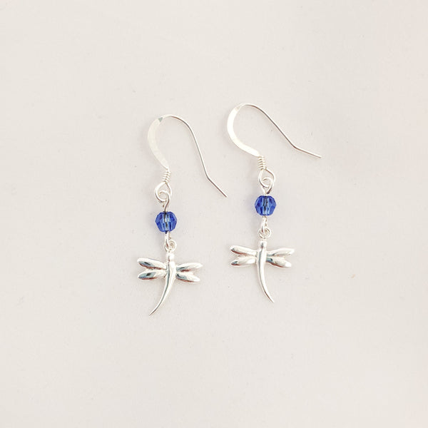 Small silver dragonfly charms hang from small round faceted blue crystals and hang from sterling silver french earring wires.
