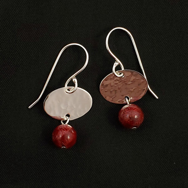 Hammered silver oval disc earrings with round coral beads hanging below.