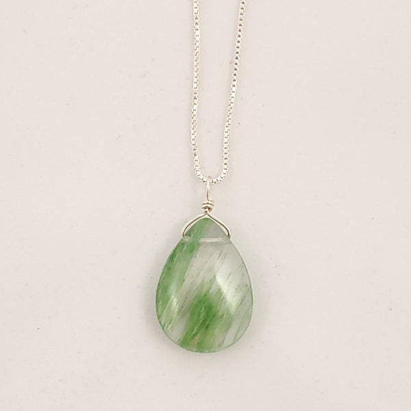 Clear teardrop pendant with green inclusion lines flowing through at a diagonal across teardrop, on box chain.