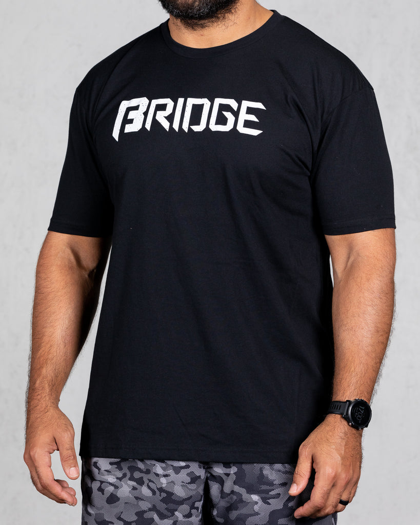 man wearing black squad tee with bridge on the front