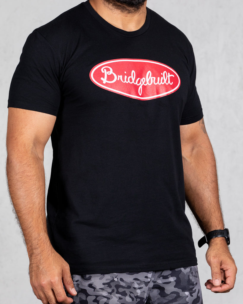 man wearing black trucker tee with red bridgebuilt design