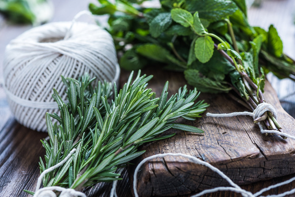 Sprig of herbs neatly arranged on a wooden board and table.
