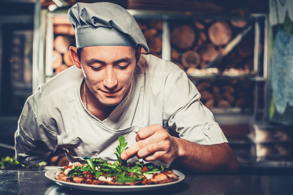 Smiling chef topping a pizza with herbs.