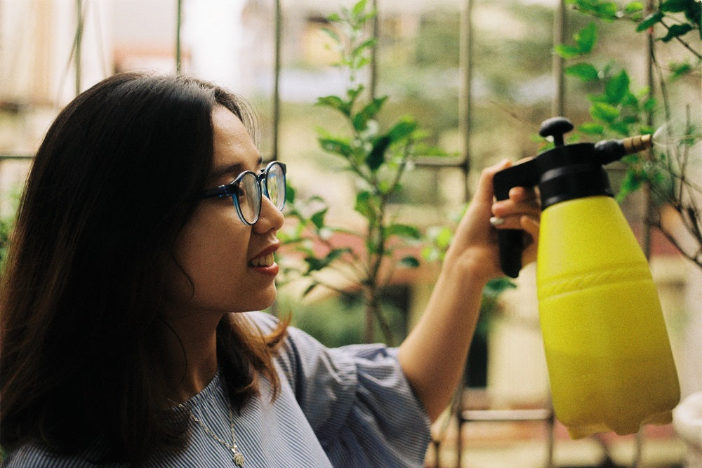 Happy woman spraying water on wall plants.