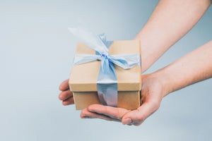 Hands holding brown and light blue gift box, present